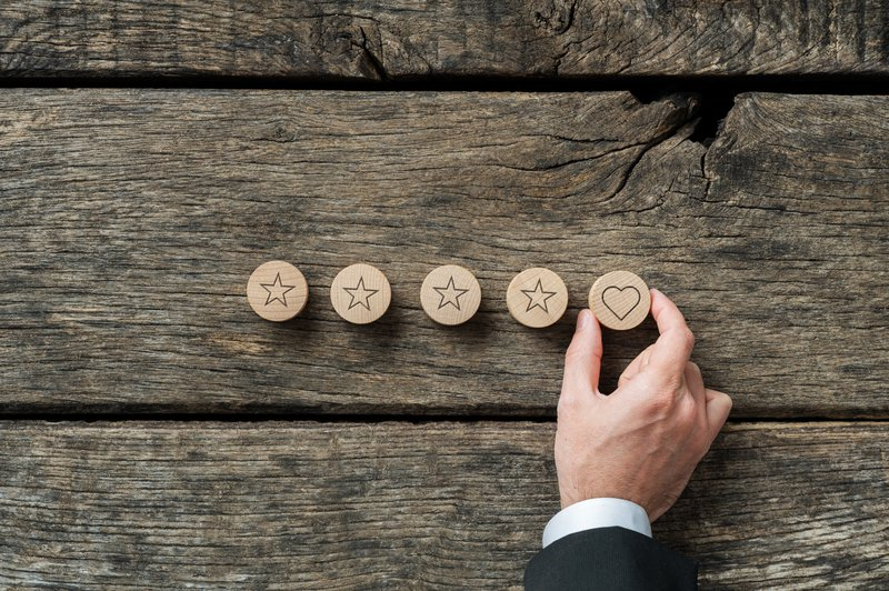 Quality and luxury conceptual image - male hand placing wooden cut circle with heart shape on it in a row of five. Over rustic wooden background.
